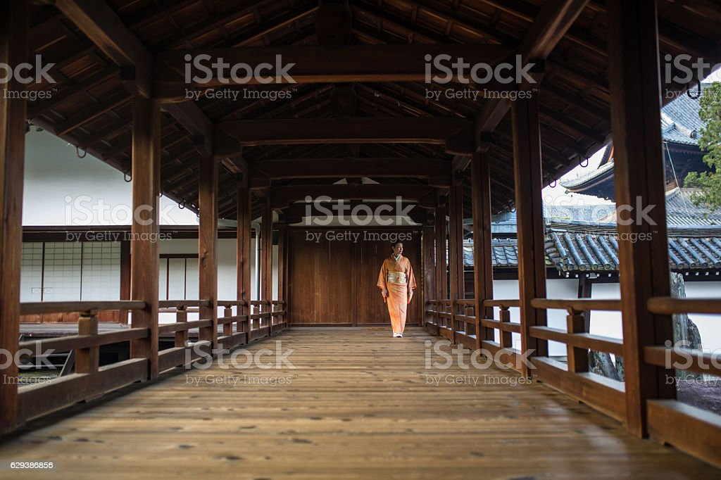 Woman in a kimono walking through a temple corridor stock photo