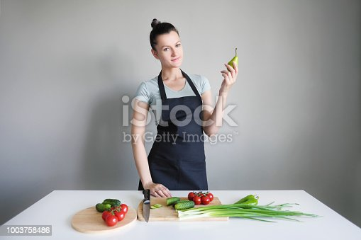 A woman in a kitchen apron holds a green pear on a gray background. On the white table are the vegetables. Cook with a smile.