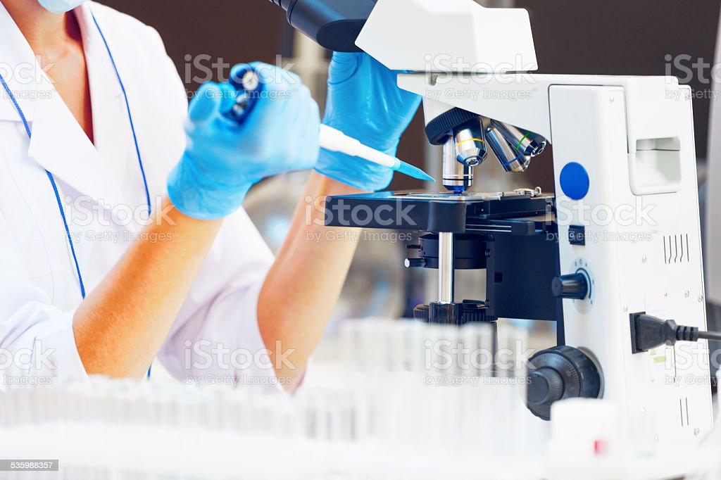 Woman in a laboratory working with microscope. stock photo