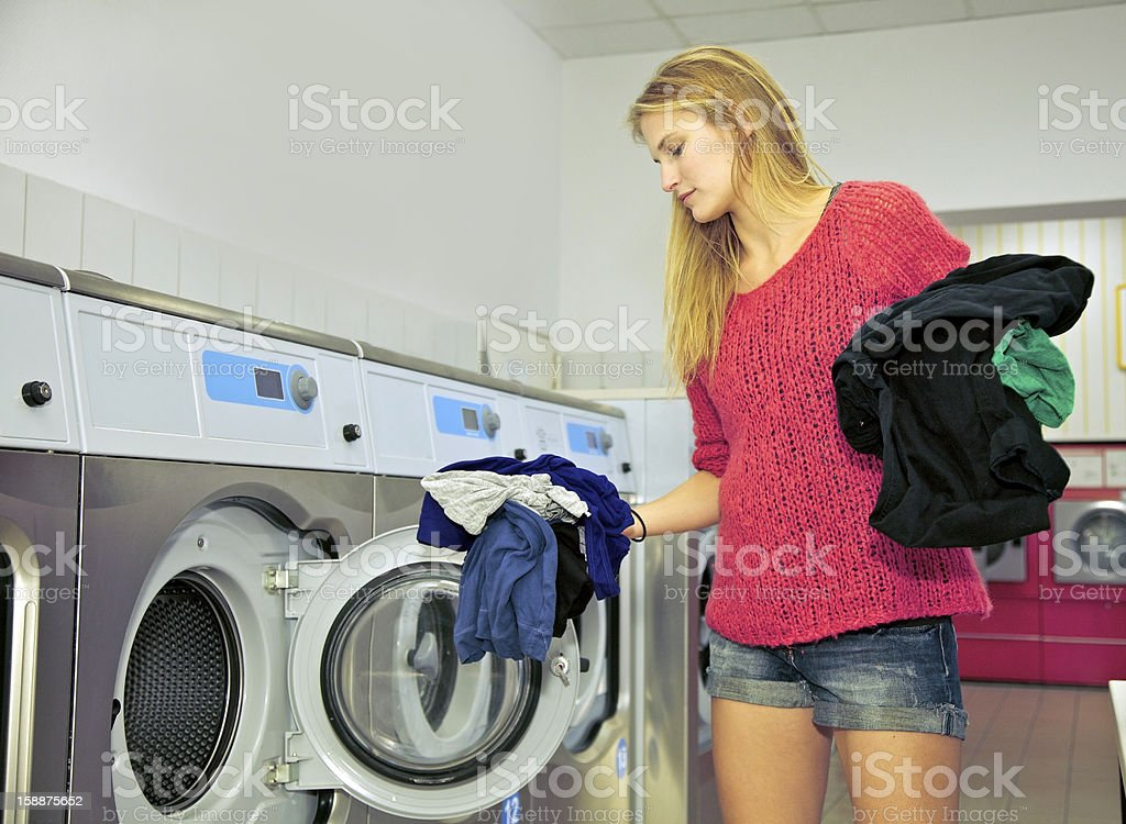 Woman in a laundromat shop. Young woman loading a washing machine inside a laundromat shop. Adult Stock Photo