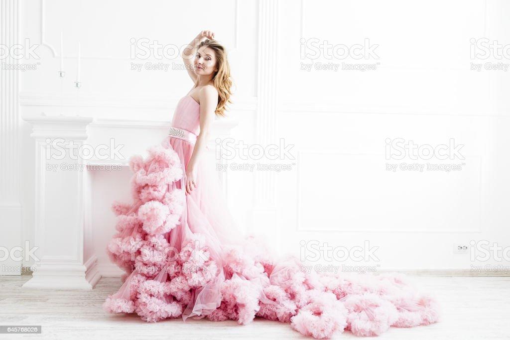 Woman in a long pale pink ruffled dress train stock photo