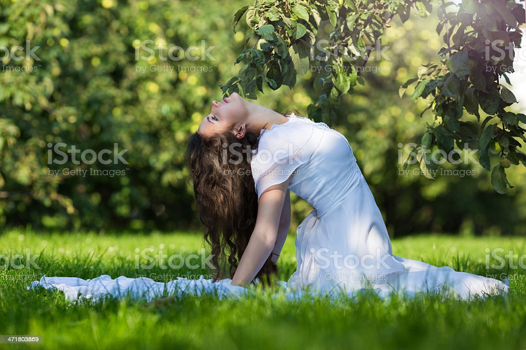 Woman in a long white dress sitting on the grass royalty-free stock photo