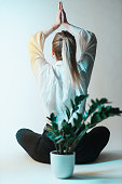 istock Woman in a lotus pose and a green plant 1288223381