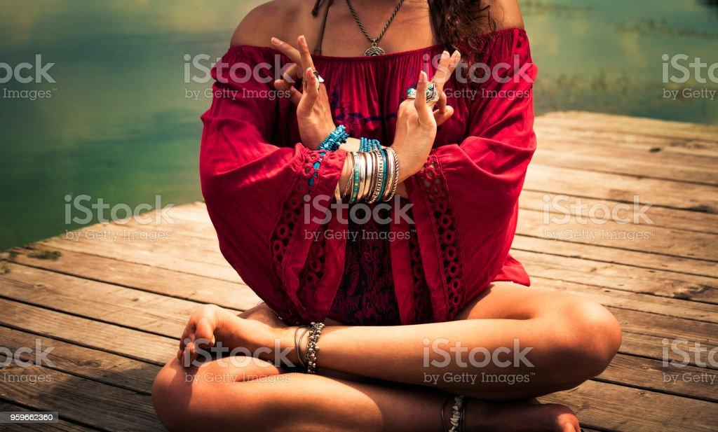 mujer en una posición de yoga meditativo con túnica roja - Foto de stock de Actividades y técnicas de relajación libre de derechos