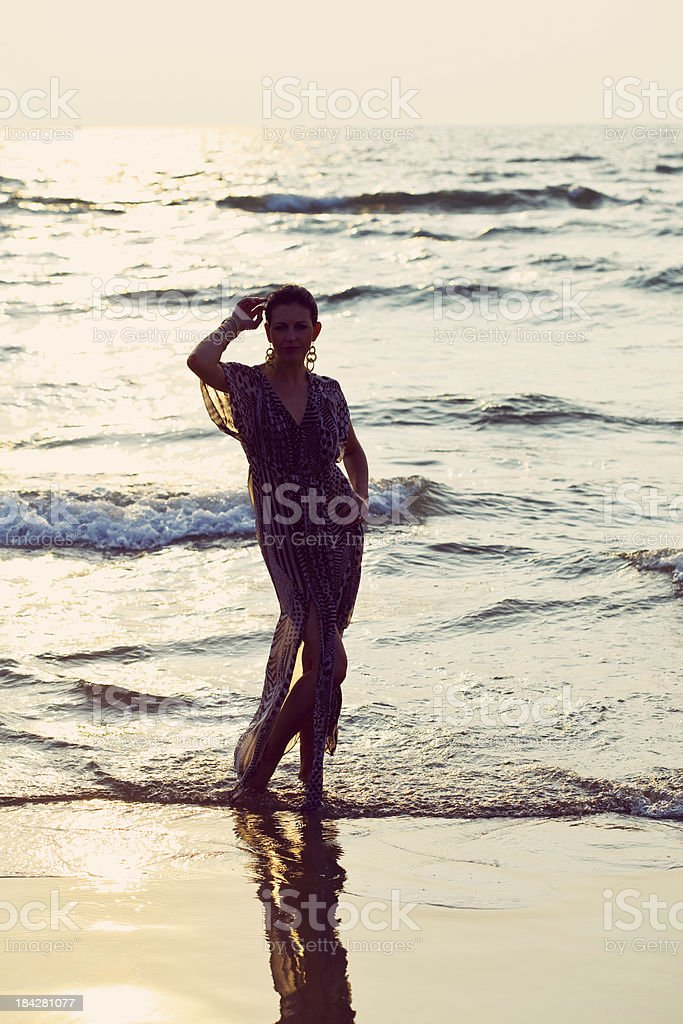 Woman in a ocean at sunset Young woman standing on the beach in the water at sunset. Adult Stock Photo