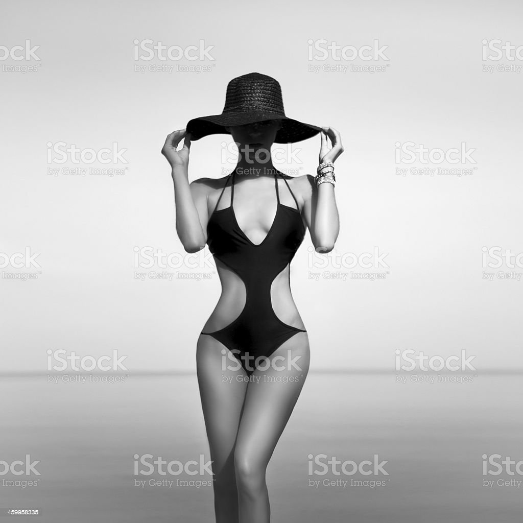 Woman in a one-piece bathing suit and sun hat by the waters stock photo