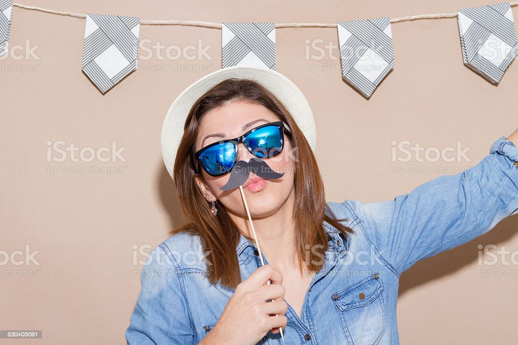 Woman in a Photo Booth party holding glasses with garland stock photo