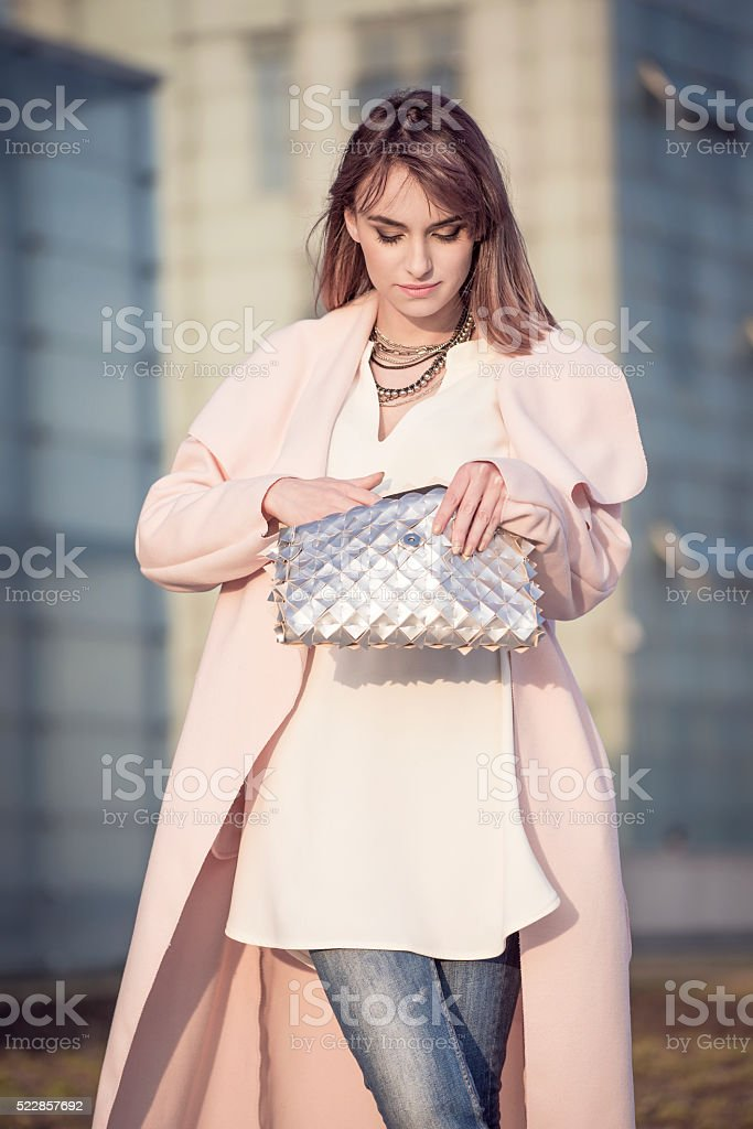 Woman in a pink coat holding handbag. stock photo