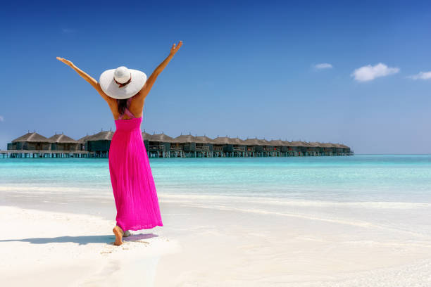 Woman in a pink summer dress stands on a tropical beach in the Maldives stock photo