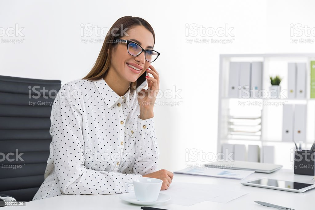 woman in a polka dot blouse is on the phone royalty-free stock photo