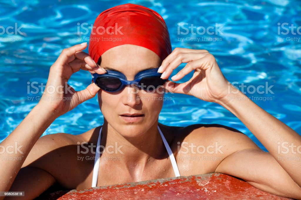 portrait of a woman in a pool with a swimming cap and swimming goggles