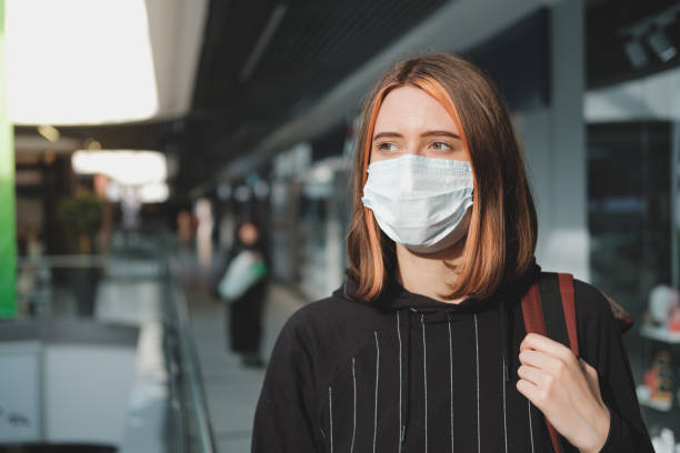 Woman in a protective face mask at a shopping mall. stock photo