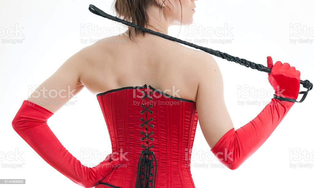 woman in a red corset and whip stock photo