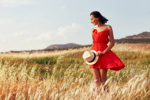 woman in a red dress walking on the field on a warm summer evening. yellow grass at sunset, the girl holding a hat in his hands. freedom and endless fields, outdoor recreation, beautiful landscape - sukienka zdjęcia i obrazy z banku zdjęć