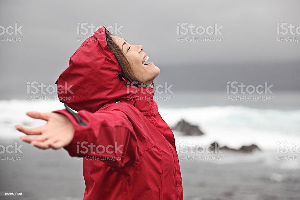 A woman in a red rain poncho enjoying the rain stock photo