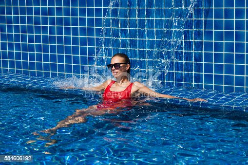 1155046257istockphoto woman in a red swimsuit in swimming pool 584606192