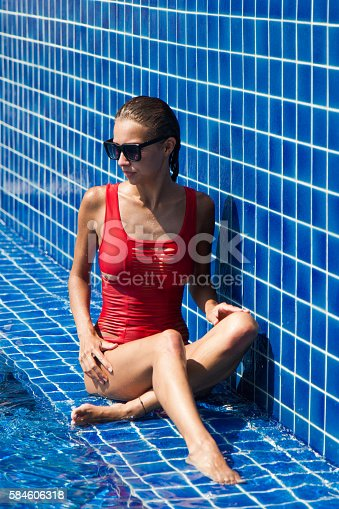1155046257istockphoto woman in a red swimsuit in swimming pool 584606318