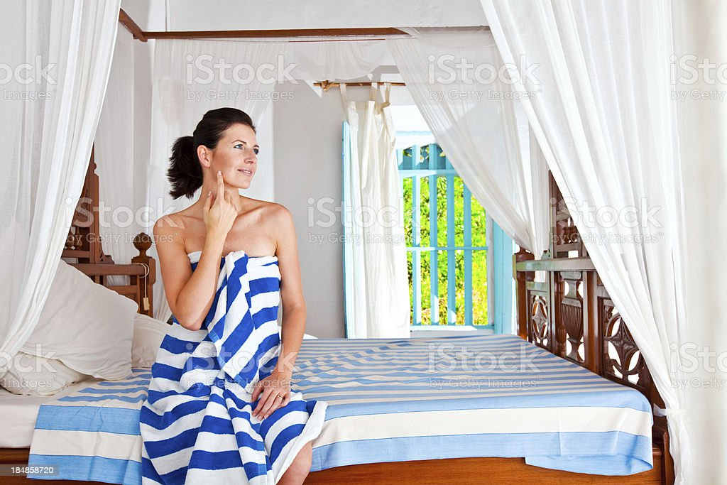 Woman in a rustic bedroom Smiling woman wearing stiped towel sitting on a bed in rustic bedroom on a tropical vacation. 25-29 Years Stock Photo