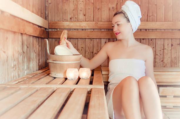woman in a sauna with a ladle - saunazubehör stock-fotos und bilder