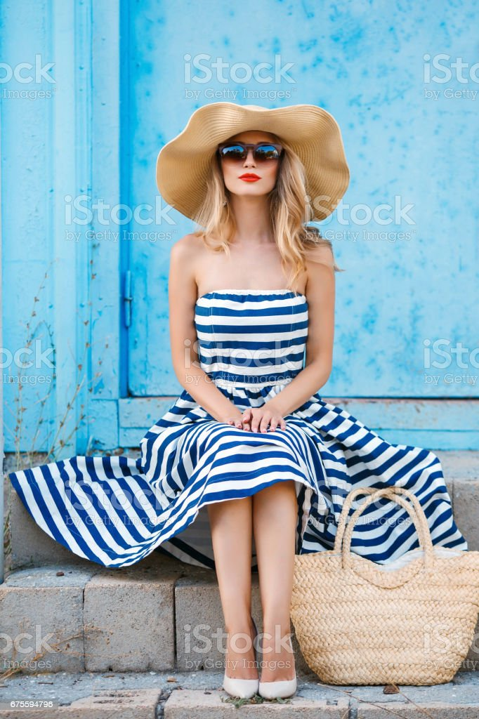 A woman in a straw hat sitting on the steps stock photo