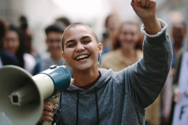 woman in a street demonstration with a megaphone - демократия стоковые фото и изображения