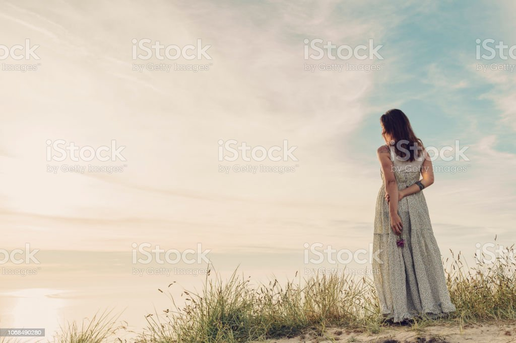 Woman in a summer dress standing on sand dunes looking out over the view at Sunset, Cornwall stock photo