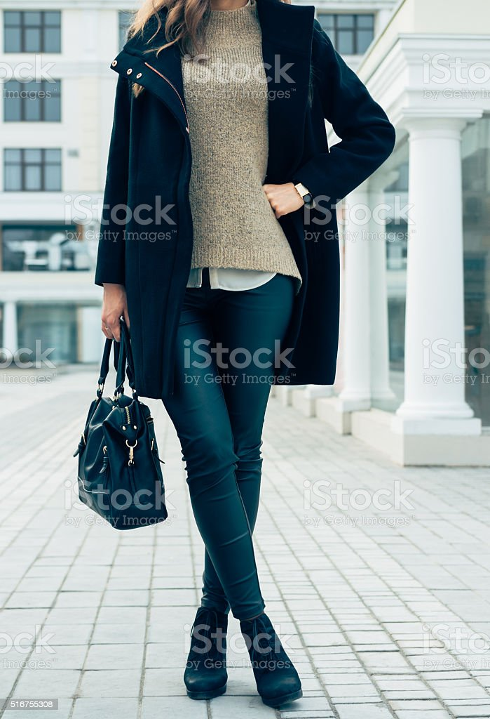 Woman in a sweater, black coat and pants stock photo
