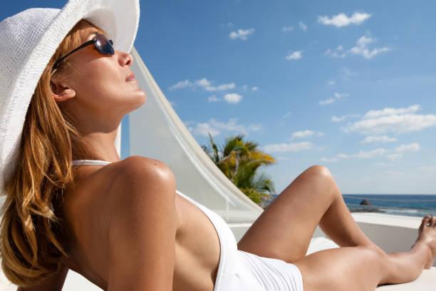 woman in a swimsuit on the sand - abbronzarsi foto e immagini stock