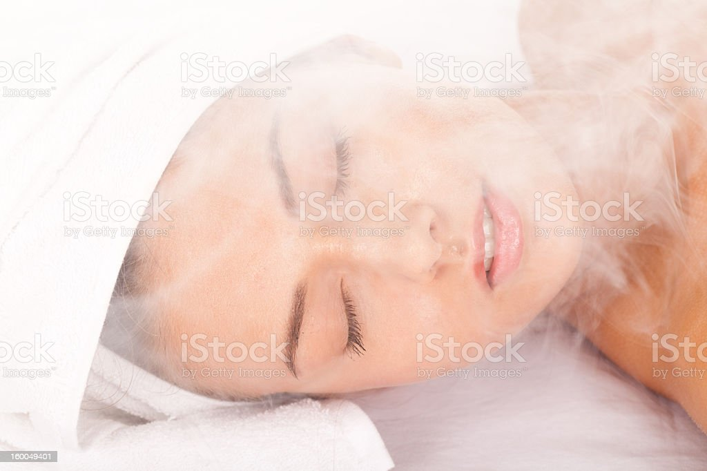 A woman in a towel relaxing in a sauna stock photo