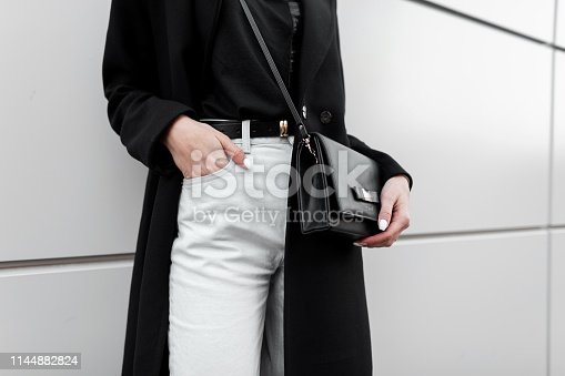 Woman in a trendy T-shirt in a black long fashionable coat in stylish white jeans with a black leather elegant bag. Trendy elegant casual outfit. Details of everyday look. Street fashion. Close-up.