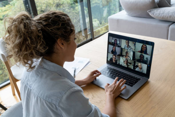 Woman in a video conference with her coworkers while working from home stock photo
