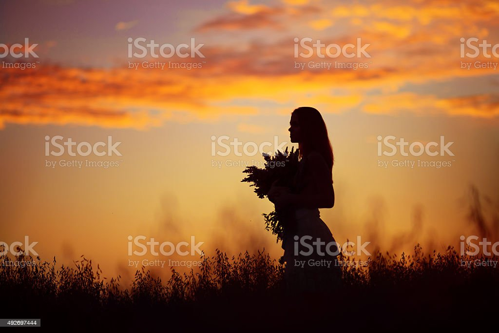 Woman in a wheat field at sunset stock photo