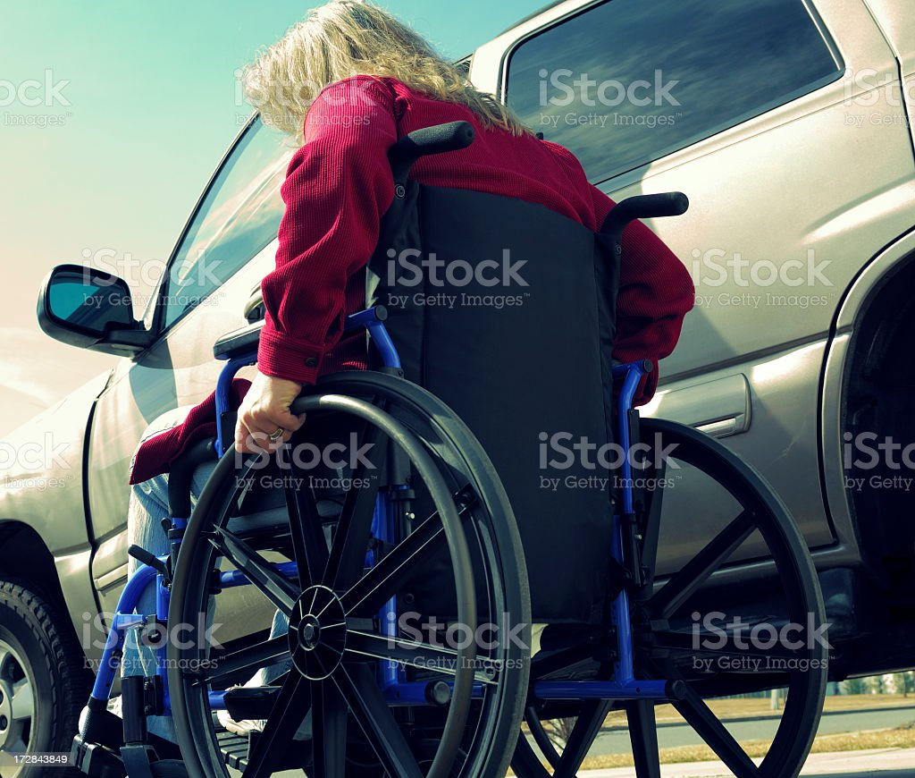 Woman in a wheelchair next to a car stock photo