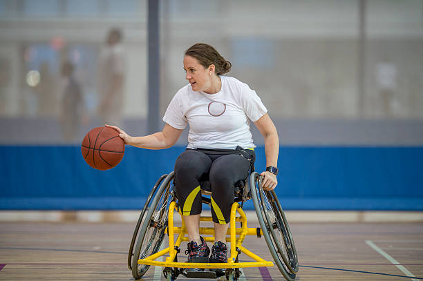 woman in a wheelchair playing basketball - wheelchair sports stock photos and pictures