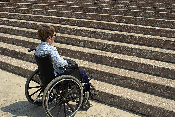 A woman in a wheelchair sitting in front of stairs inaccessible building access discriminatory stock pictures, royalty-free photos & images