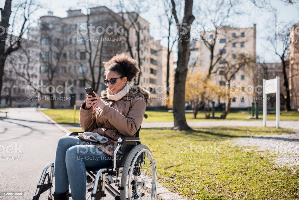 Frau in einem Rollstuhl mit Smartphone im park – Foto