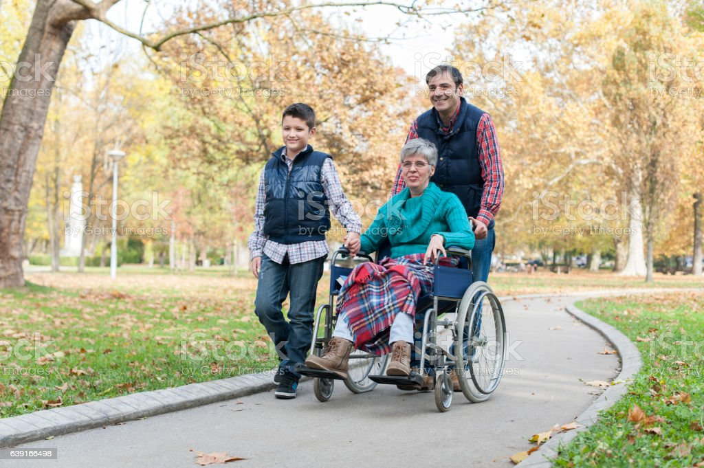 Woman in a wheelchair with his son and grandson stock photo
