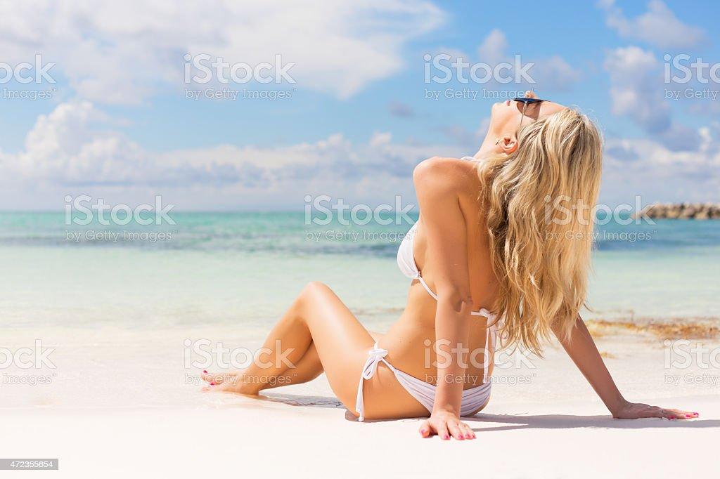 A woman in a white bikini on the beach stock photo