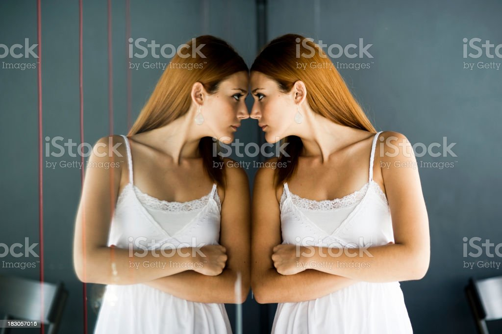Woman in a white dress staring at her own reflection royalty-free stock photo