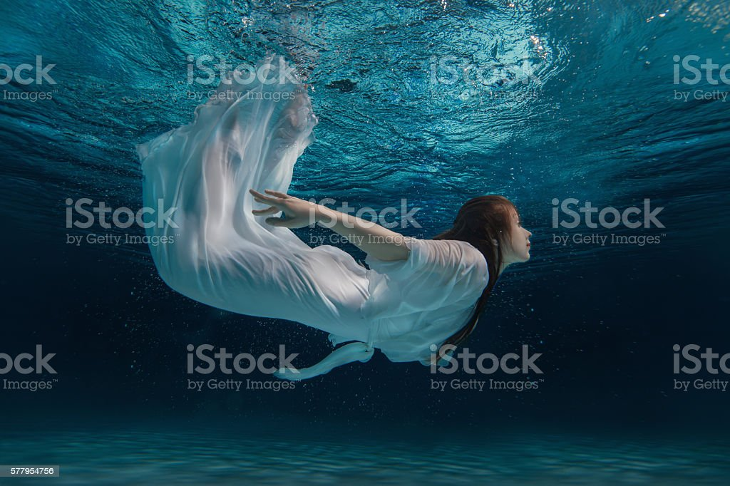 Woman in a white dress under water. stock photo