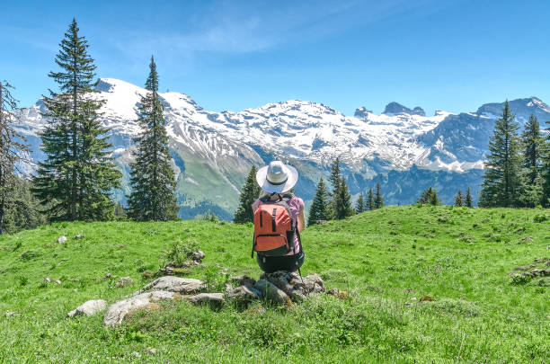 woman in a white hat is sitting on a meadow Swiss Alps. A woman in a white hat is sitting on a green meadow, admiring the mountain scenery. Engelberg Resort bavarian alps stock pictures, royalty-free photos & images