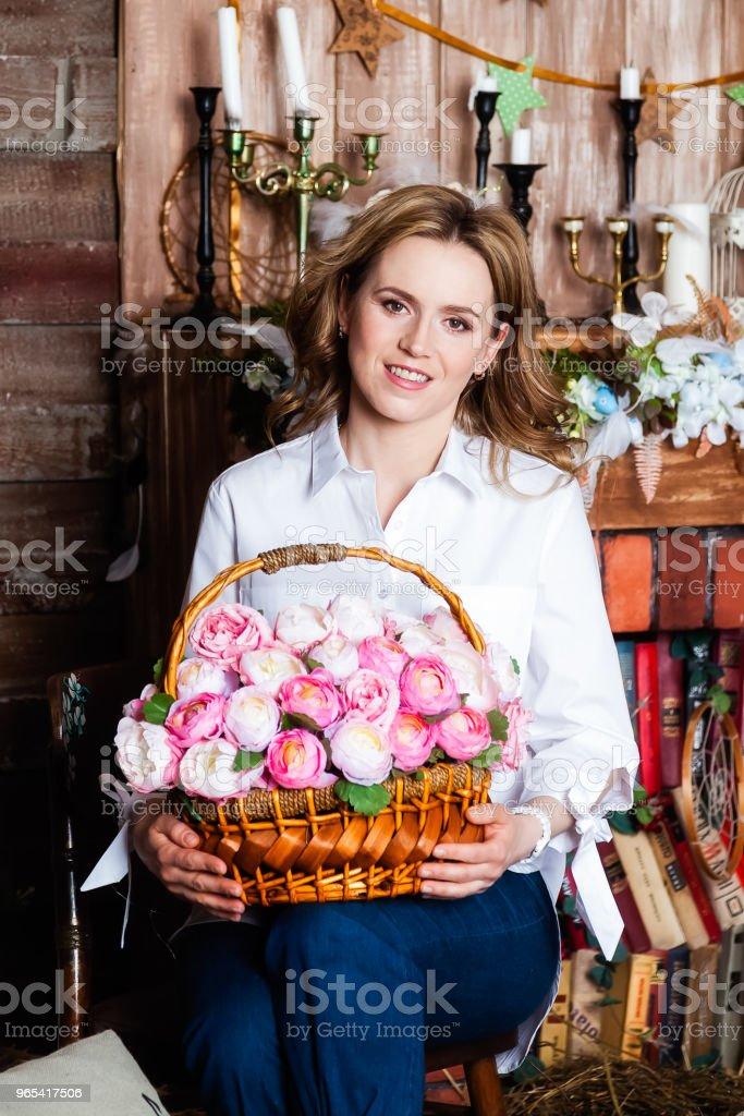 穿著白襯衣的女人坐在椅子上, 微笑著看著相機。 - 免版稅一個人圖庫照片