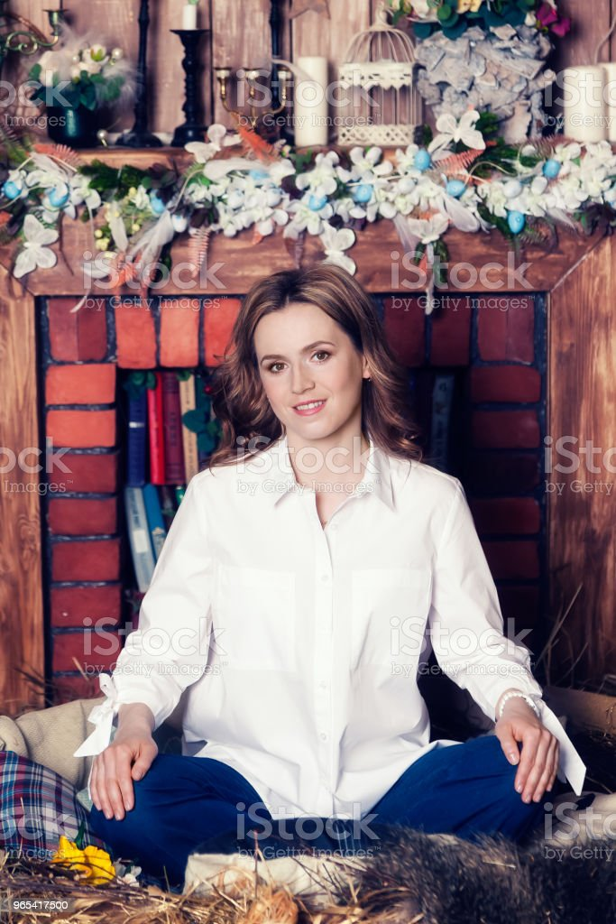 A woman in a white shirt is sitting on the floor smiling and looking at the camera royalty-free stock photo