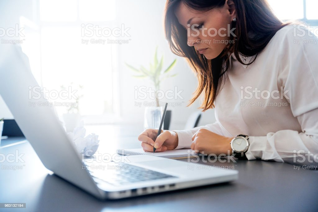 Woman in a white suit writing in her clipboard. royalty-free stock photo