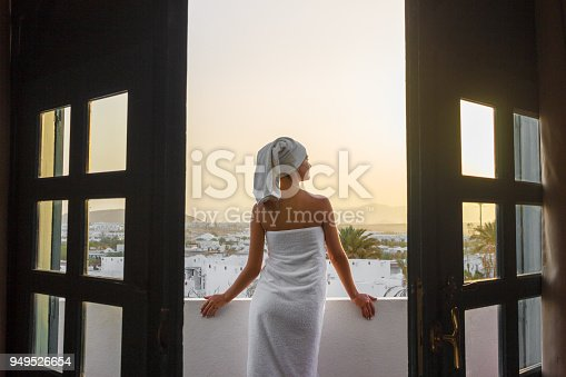 A woman in a white towel is standing on a terrace overlooking the mountains in a hotel room.
