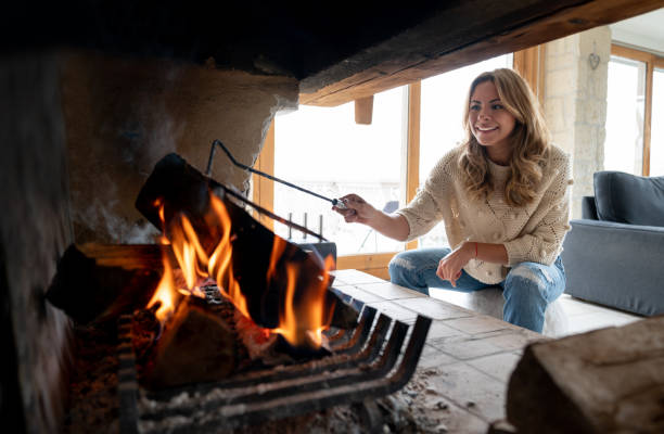 Woman in a winter lodge burning logs and looking happy Portrait of a young woman in a winter lodge burning logs to keep warm and looking happy - lifestyle concepts chalet stock pictures, royalty-free photos & images