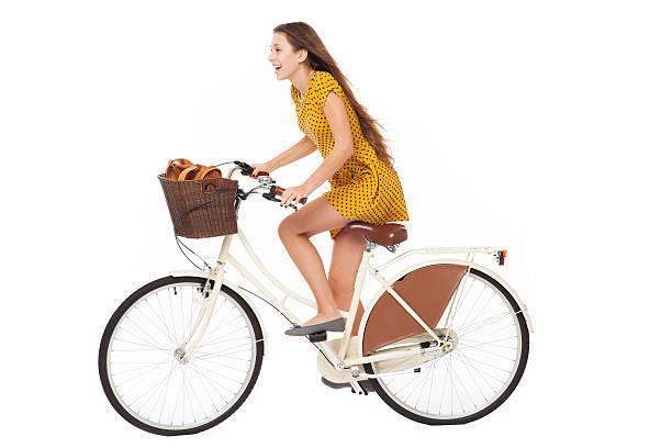 Woman in a yellow dress riding a bike stock photo