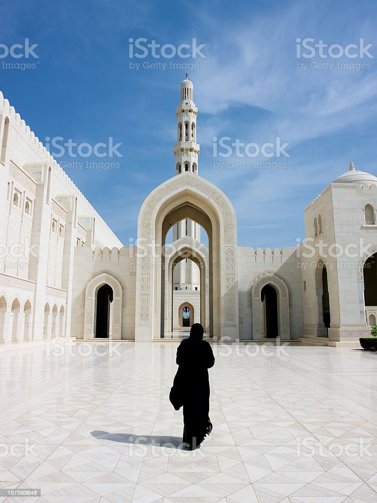 Woman in Abaya Cloak walking towards Archway of Grand Mosque stock photo