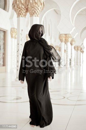 young muslim woman in abaya, walking through mosque.
