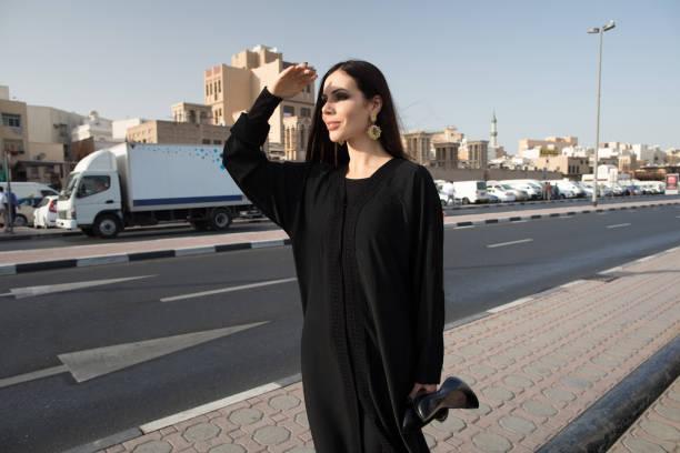 Femme en abaya regarder la route. - Photo